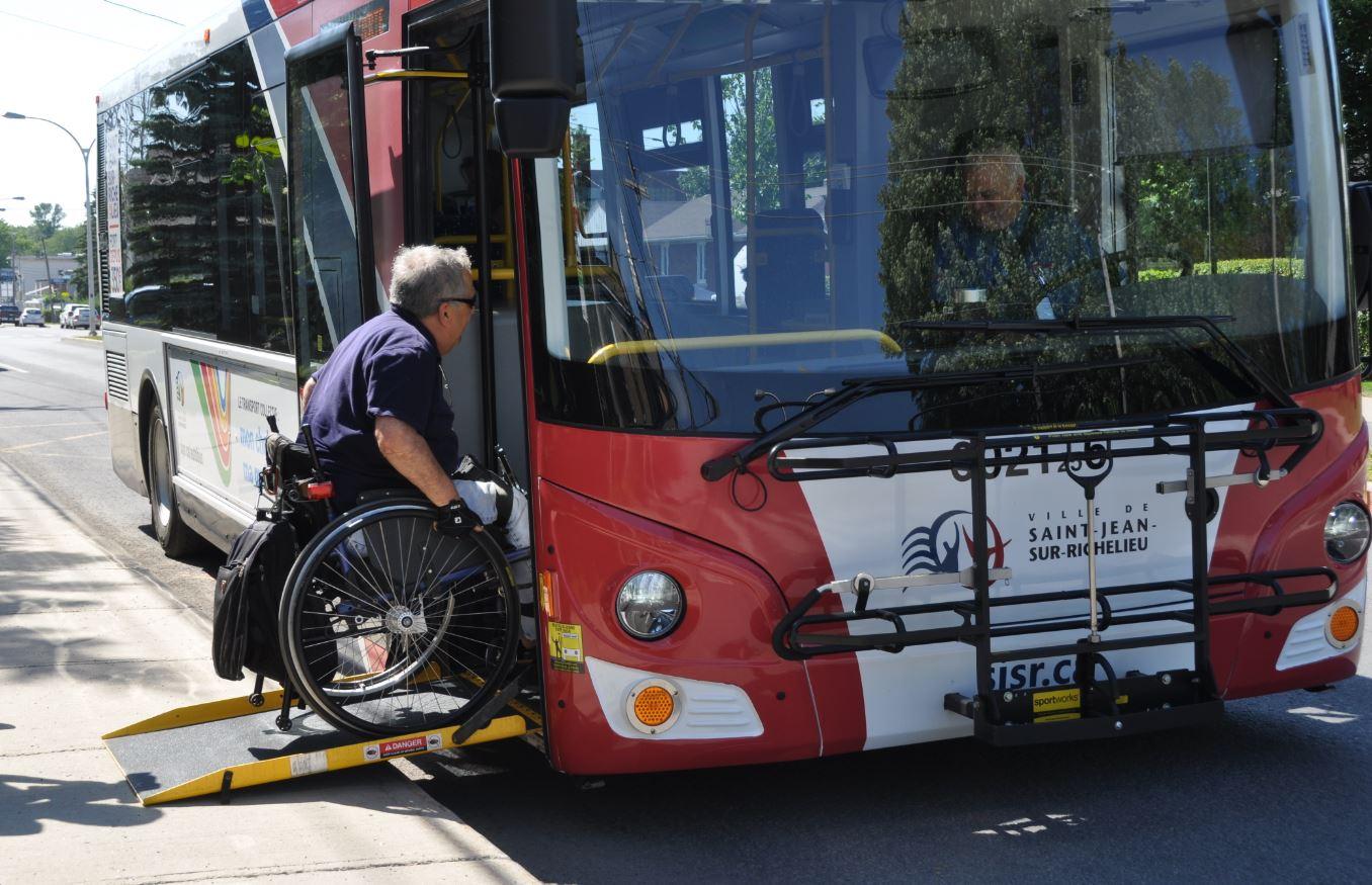 Un homme en fauteuil roulant, montant à bord d'un autobus à l'aide de la rampe d'accès.
