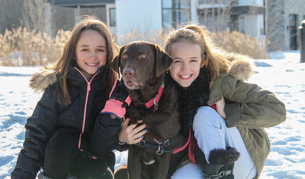 Deux jeunes filles souriante en compagnie de leur chien.