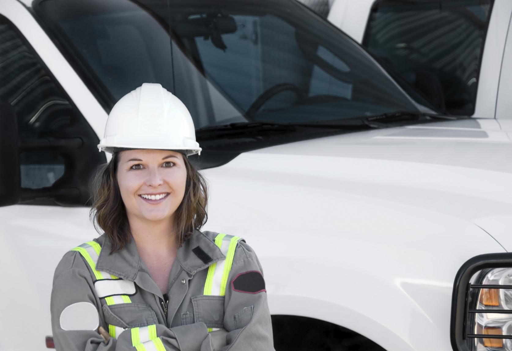 Une travailleuse devant son véhicule de service.