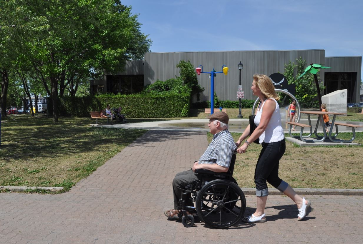 Un homme en fauteuil roulant, poussé par une accompagnatrice.