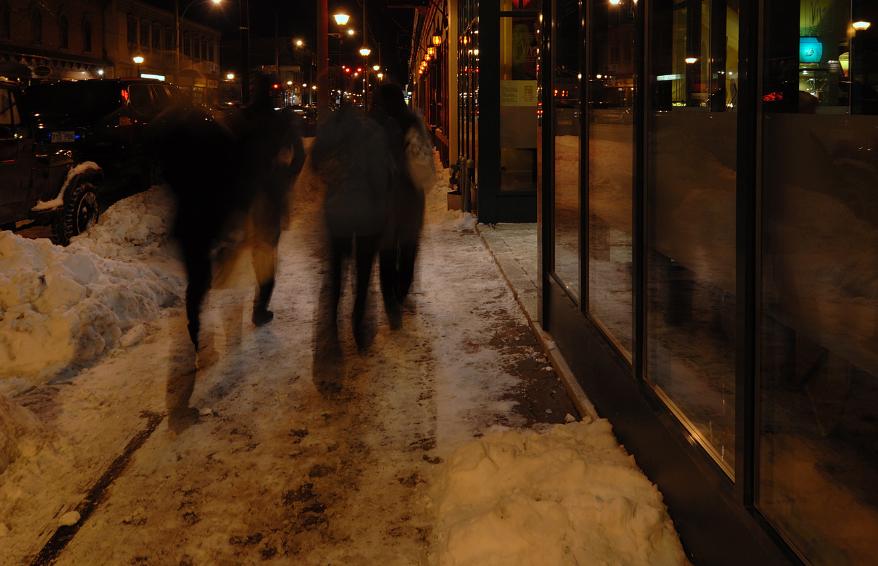 Des voitures stationnées de nuit en hiver.