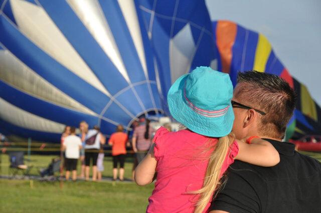 Un père et sa fille regardent une envolée de montgolfières.
