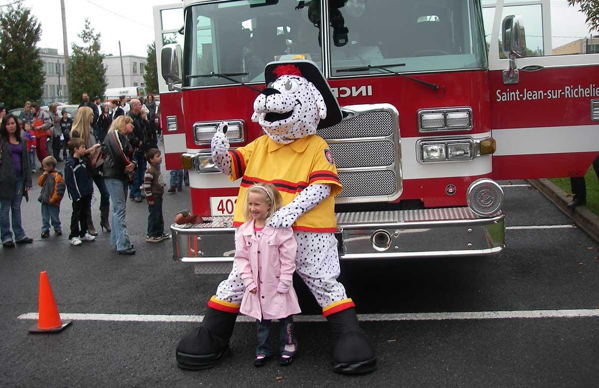 Une fillette et une mascotte devant un camion de pompiers.